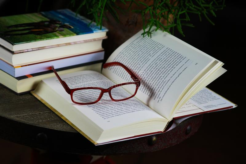 View on open book with red reading glasses and stack of travel books stock images
