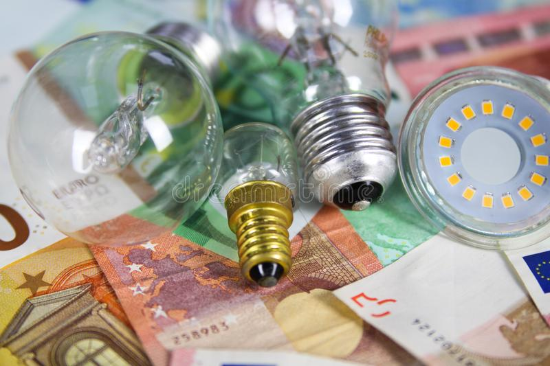 VIERSEN, GERMANY - MAY 20. 2019: Power supply cost concept - Electric light bulbs on Euro paper money bank notes stock photo