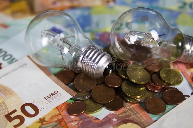 VIERSEN, GERMANY - MAY 20. 2019: Power supply cost concept - Electric light bulbs on Euro paper money bank notes and pile of coins royalty free stock photos