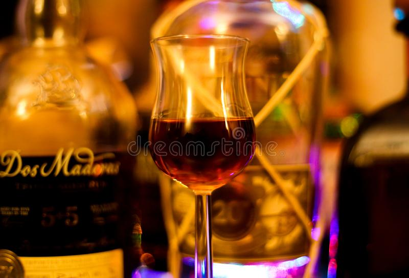 Close up of isolated shot glass for rum tasting. Blurred bottles background stock photo