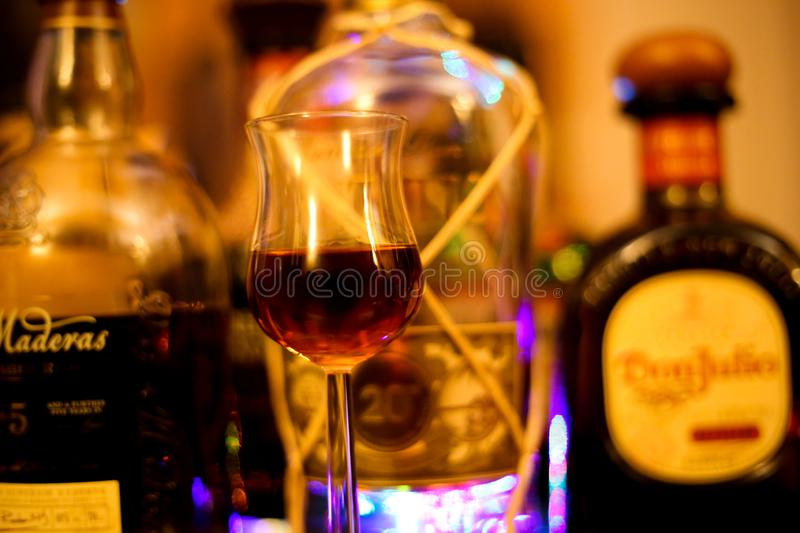Close up of isolated shot glass for rum tasting. Blurred bottles background stock image