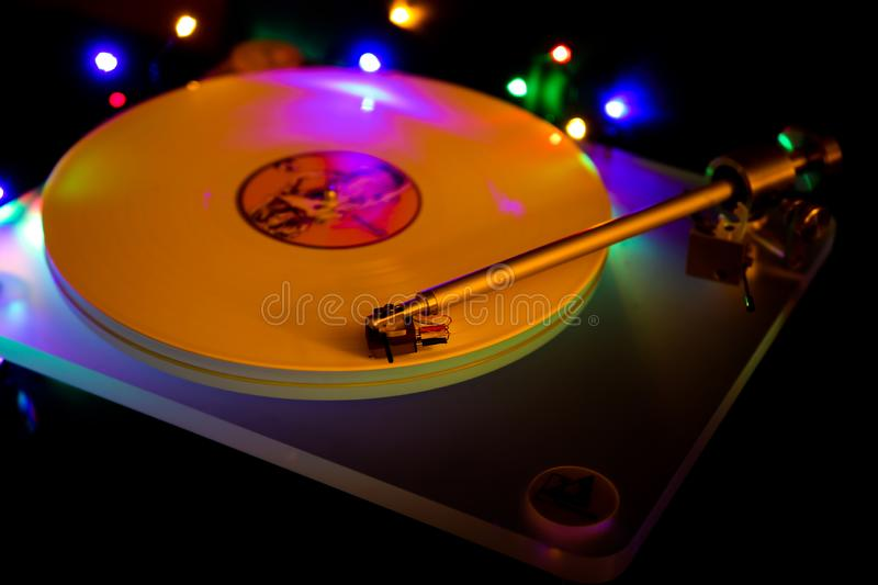 Close up of isolated vintage retro record player with white vinyl lp. Shiny colorful bokeh background royalty free stock photography