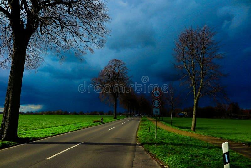 VIERSEN, NIEMCY - Ciemny niebo z gradowymi peleng chmurami nad wiejską drogą i nadzy drzewa ogłasza grzmot szalejemy obraz royalty free