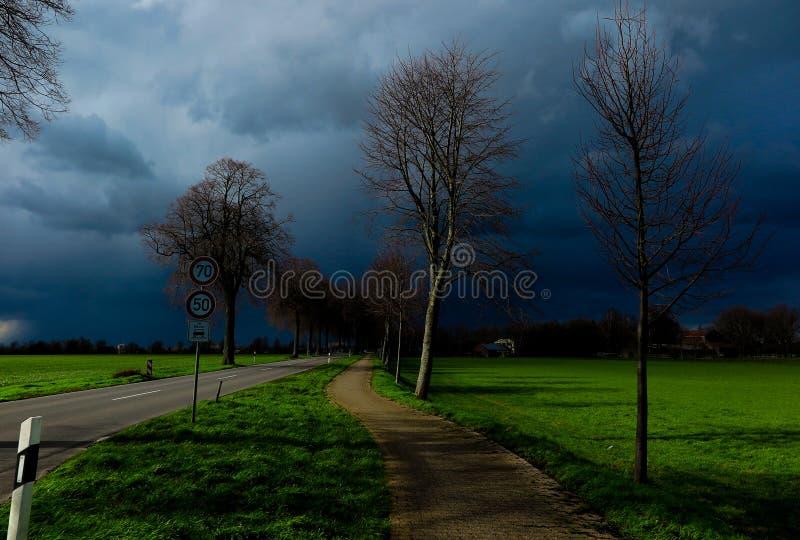 VIERSEN TYSKLAND - mörk himmel med hagel uthärda moln över landsvägen och kala träd som meddelar åskastormen royaltyfria foton
