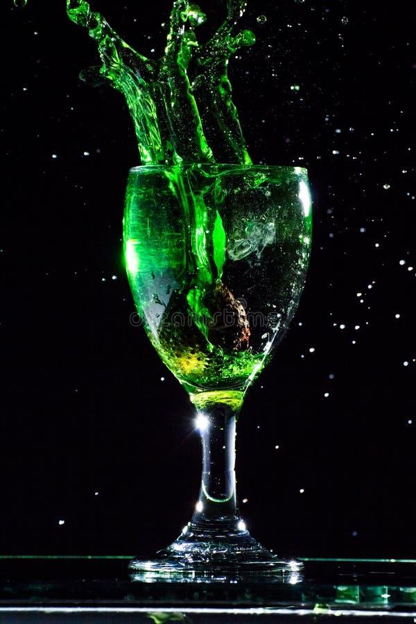 Vierta el agua verde en un vidrio, chapoteo del agua en vidrio foto de archivo libre de regalías