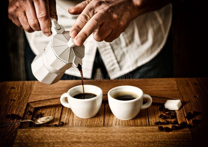 Vierta el café express en las tazas - bebida italiana tradicional - foco selectivo - efecto desaturado foto de archivo