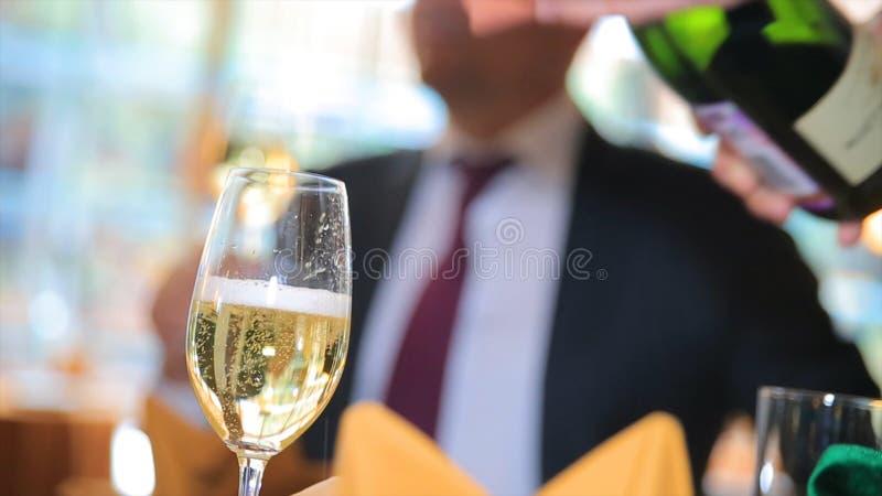 Vierta el champán en un vidrio Champán de colada del camarero en el vidrio, primer Champán que vierte en vidrio imagen de archivo