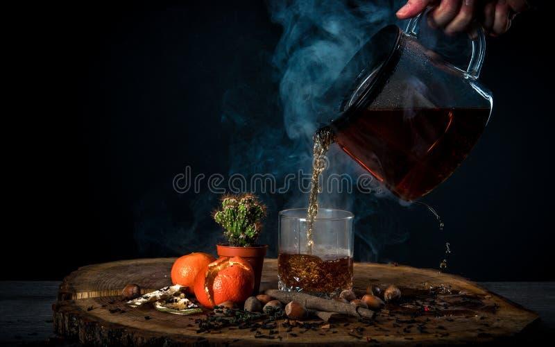 Vierta el té caliente en un vidrio foto de archivo