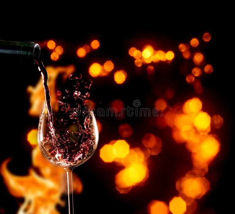 Vierta el vino tinto en copa delante del fuego imagen de archivo libre de regalías