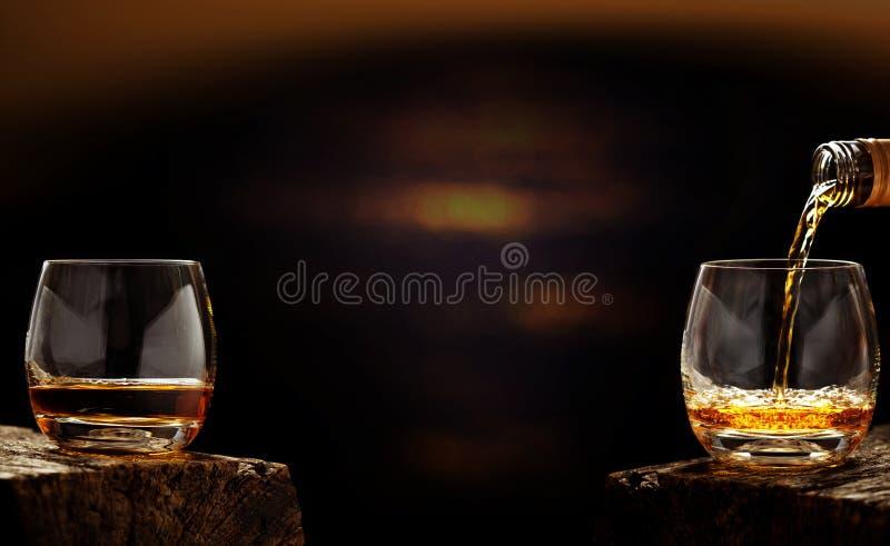 Vierta el whisky fuera de la botella en vidrio del whisky fotografía de archivo libre de regalías