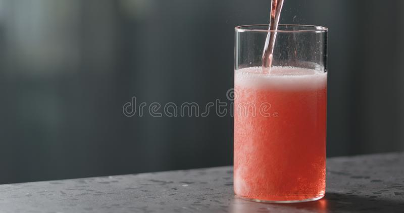 Vierta la sidra de berry en vidrio en la contraparte de terrazo con espacio de copia imagen de archivo