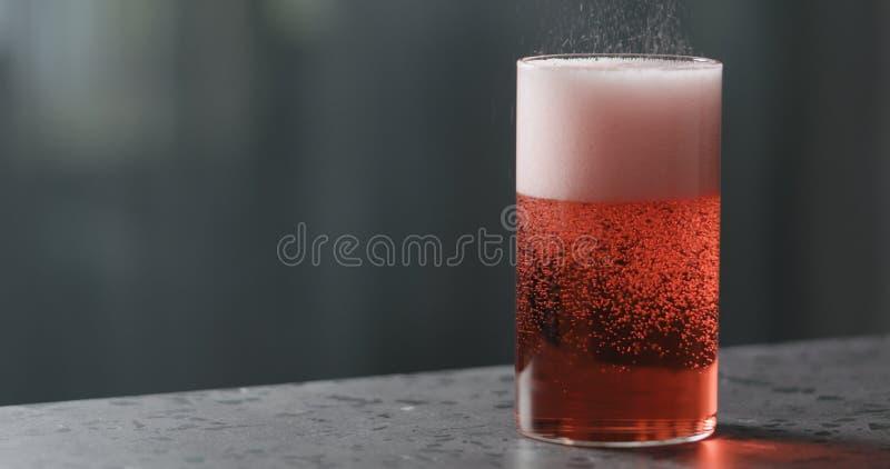 Vierta la sidra de berry en vidrio en la contraparte de terrazo con espacio de copia foto de archivo