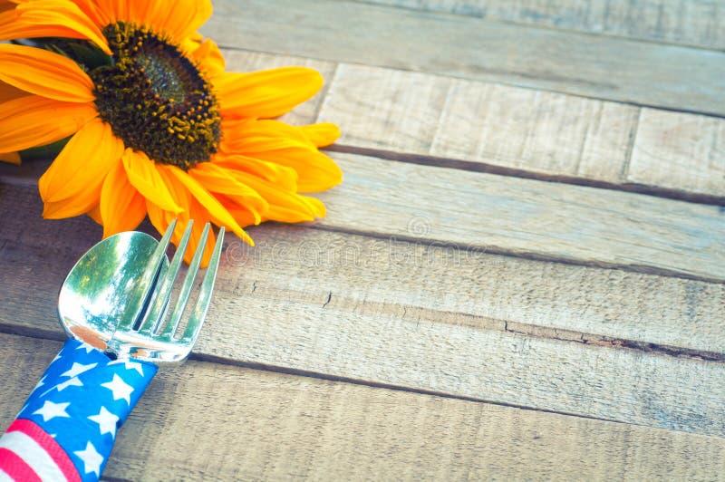 Viertel des Juli-Picknick-oder BBQ-Tabellen-Gedecks mit Rotem, weißem und Blauem, Sternenbanner Serviette um Gabel und Messer mi stockbilder