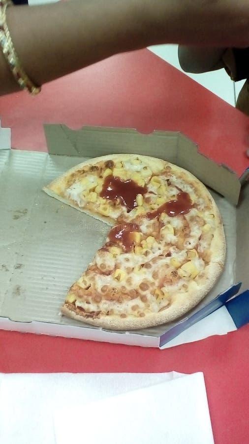 Viertel drei der gelieferten Pizza mit etwas rotem sause, das auf der roten Tabelle bleibt lizenzfreie stockfotos