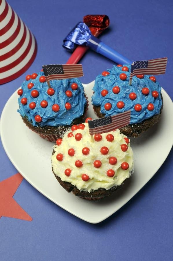 Viertes 4. der Juli-Parteifeier mit den roten, weißen und blauen Schokoladenkleinen kuchen - Luftaufnahme über Herzformplatte. stockfotografie
