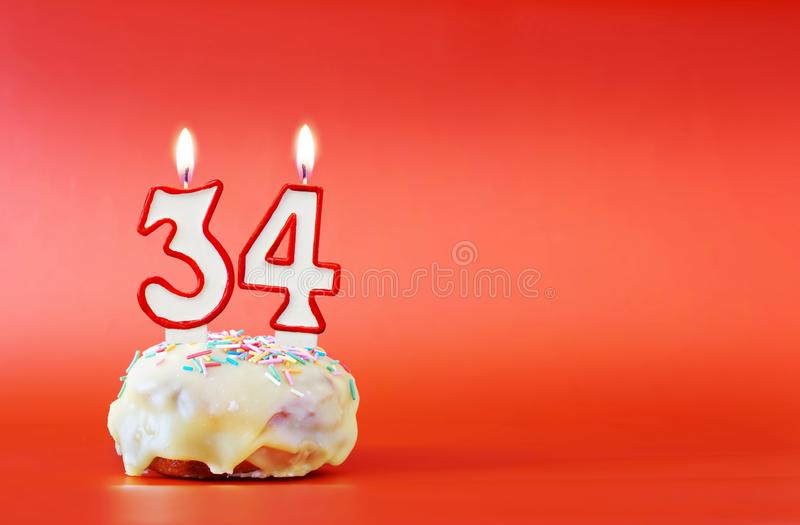 Vierunddreißig Jahre Geburtstag Kleiner Kuchen mit weißer brennender Kerze in Form von Nr. 34 lizenzfreie stockfotos