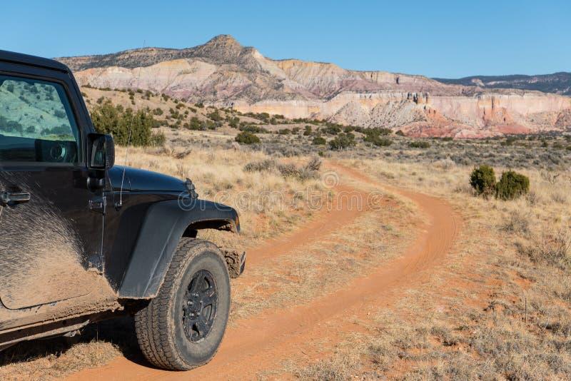 Vierwielaandrijvingvoertuig op een buigende landweg die naar een kleurrijke hoge woestijnpiek drijven in Spookboerderij, New Mexi stock foto