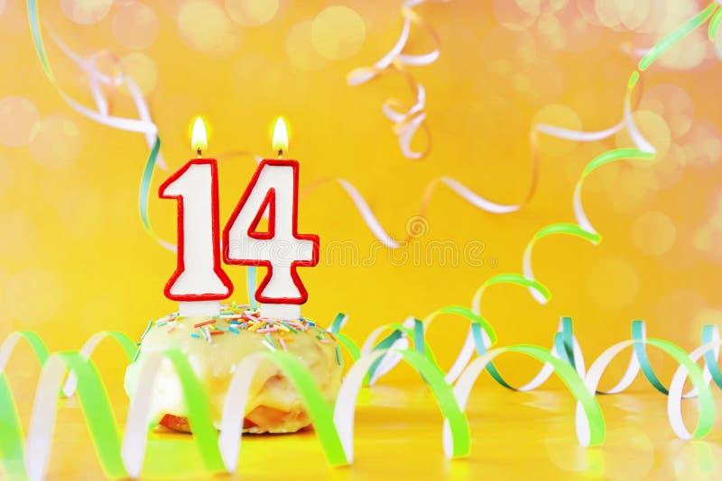 Vierzehn Jahre Geburtstag Kleiner Kuchen mit brennenden Kerzen in Form von Nr. 14 lizenzfreies stockbild