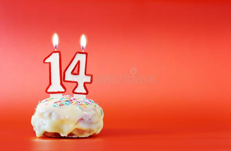Vierzehn Jahre Geburtstag Kleiner Kuchen mit weißer brennender Kerze in Form von Nr. 14 stockbild
