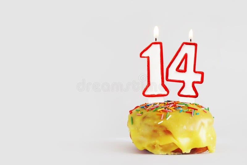 Vierzehn Jahre Jahrestag Geburtstagskleiner kuchen mit weißen brennenden Kerzen mit roter Grenze in Form von Nr. vierzehn stockfotos