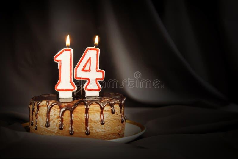 Vierzehn Jahre Jahrestag Geburtstagsschokoladenkuchen mit weißen brennenden Kerzen in Form von Nr. vierzehn stockbilder