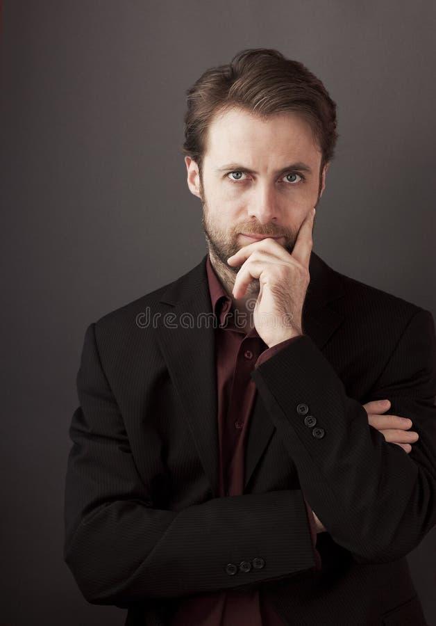 Vierzig Jahre alte Geschäftsmann, die auf einem grauen Hintergrund stehen lizenzfreie stockbilder