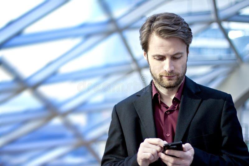 Geschäftsmann innerhalb des Büros, das an einem Handy schaut lizenzfreies stockfoto