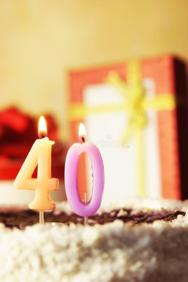 Vierzig Jahre Geburtstagkuchen mit brennenden Kerzen stockbild