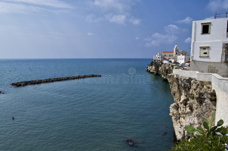 Vieste, Gargano, Apulia, Italy: Vieste beautiful town with cliffs, sea and clouds during a sunny day stock image