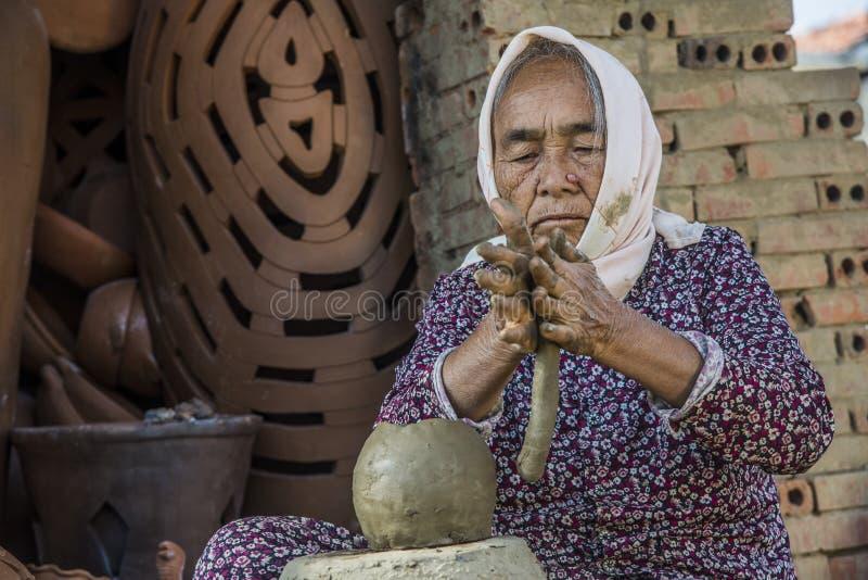 Vietnam December 2017: Local Vietnamese woman molding pot from clay mixture in her factory, Vietnam stock photo