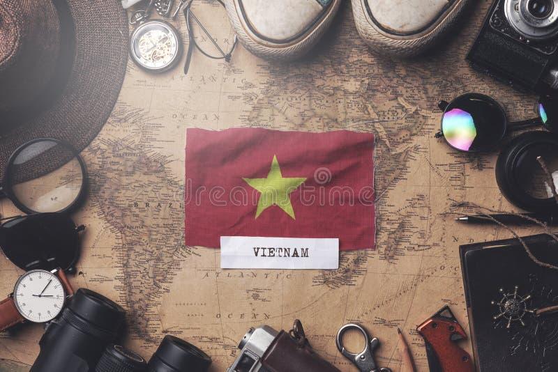Vietnam Flag Between Traveler`s Accessories on Old Vintage Map. Overhead Shot.  stock photography