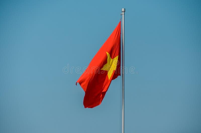Vietnam flagga på pol på blå bakgrund arkivbilder