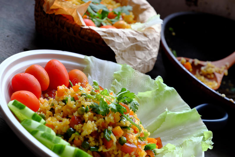 Vietnam food, fried rice. Make from rice, egg, sausage, dried shrimp, bean, cucumber, tomato, carrot and scallion, close up of dish on wooden background royalty free stock images