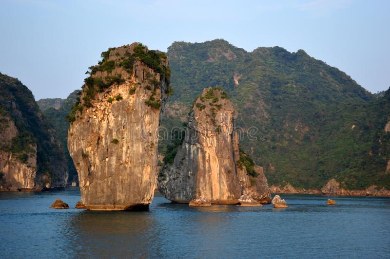 Vietnam - Ha Long Bay -evening light two small distinctive limestone karsts in foreground with larger islands in the background. Ha Long Bay AUCO cruise -evening stock photos