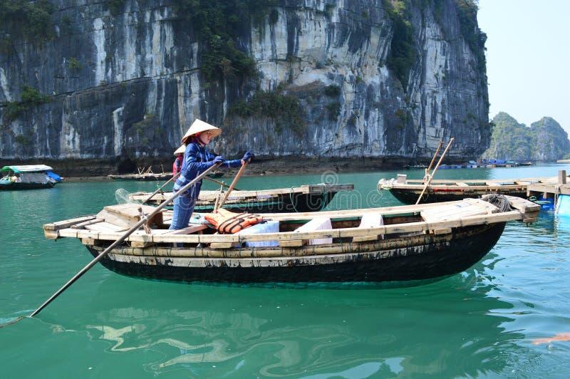 Vietnam - Ha snakt de Baai - sluit toerist het roeien omhoog boot en dame die de boot onder kalksteenkarsts roeien royalty-vrije stock foto's