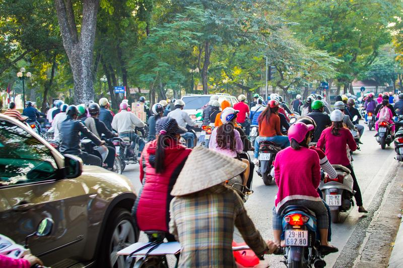 Vietnam, Hanoi, December 07, 2016: A lot of motorcyclists and vehicles drive at the street of city. Asia, asian, background, bike, building, busy, chaotic royalty free stock photography