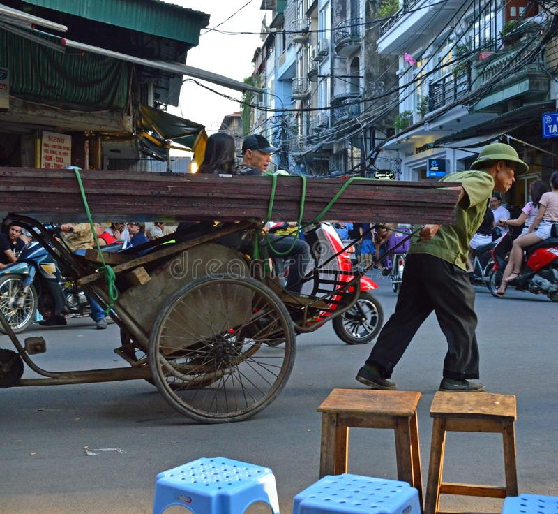 Vietnam - Hanoi - typical street scene from the Old Quarter - man pulling rickshaw full of metal stock photography