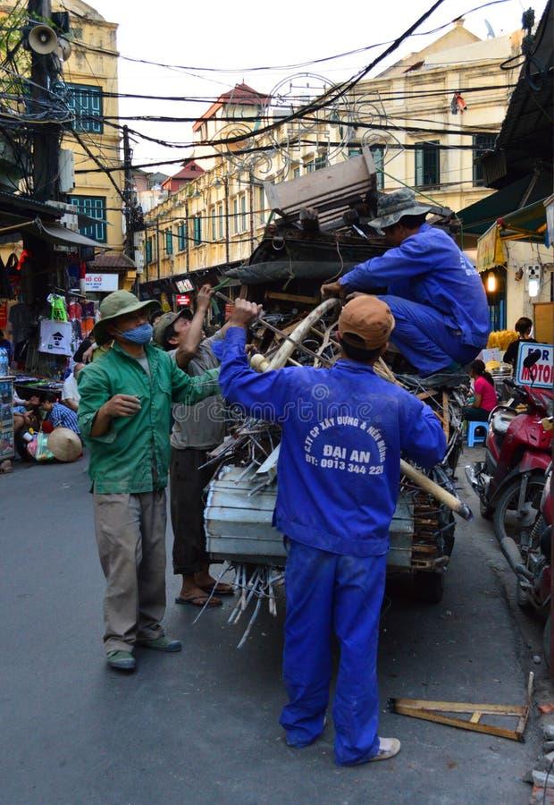 Vietnam - Hanoi - typisk gataplats från den gamla fjärdedelen - män som traver på metall och trä på en rickshaw arkivfoto