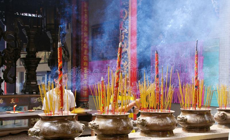 HO CHI MINH CITY, VIETNAM - JANUARY 5. 2015: Woman praying behind pots with burning and fuming incense sticks in buddhist chinese royalty free stock photos