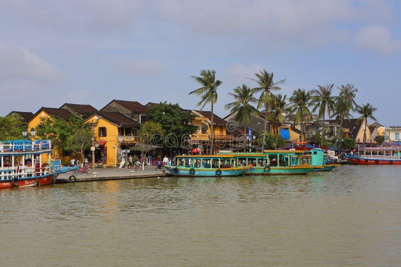 Vietnam Hoi An - Januari 2017: Fartygflöten på Bon River mot bakgrunden av hus på stranden i staden av Hoi An arkivbild
