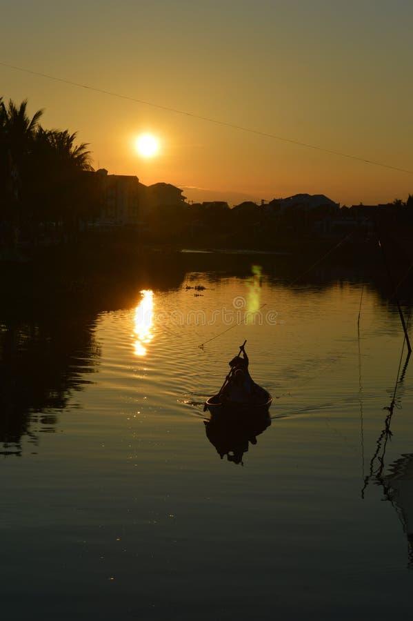 Vietnam - Hoi un escénico del pequeño barco de pesca del rowing en silueta en Thu Bon River en la puesta del sol imagen de archivo