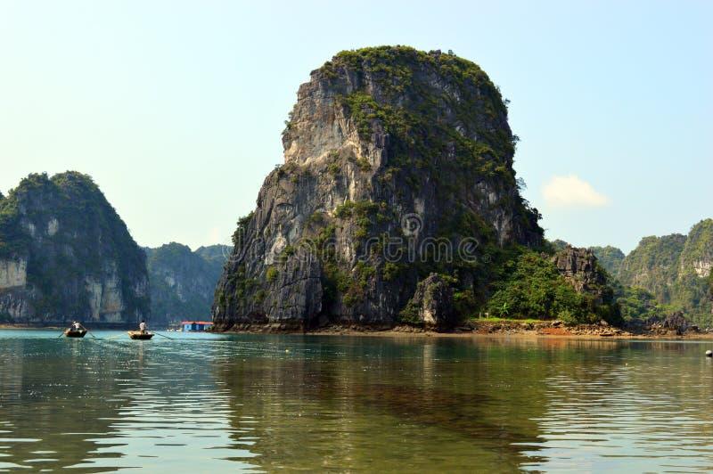 Vietnam - karsts largos de la piedra caliza de la bahía de la ha con los barcos de rowing cerca del pueblo pesquero flotante de V foto de archivo