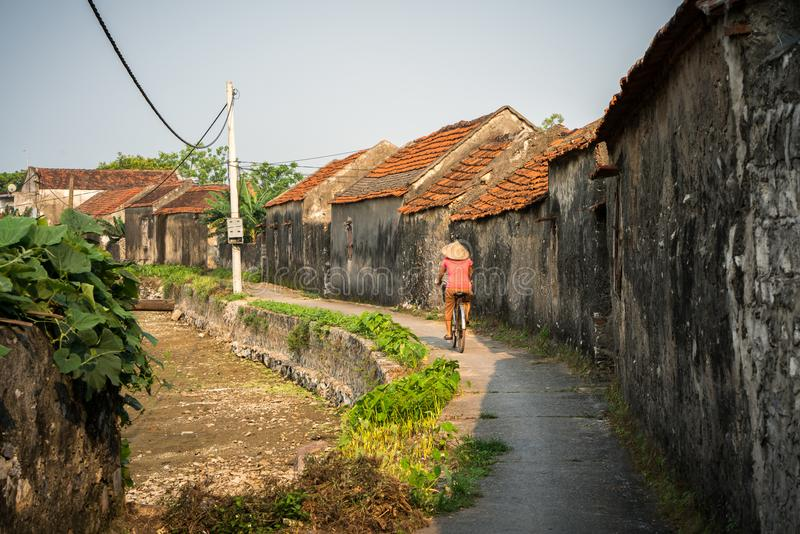 Vietnam landscape with old aged houses and woman cycling on road in village.  royalty free stock images