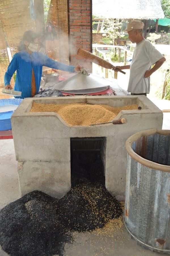 Vietnam- - Mekong-Deltamann und -dame, die Reispapierverpackungen herstellen stockbild