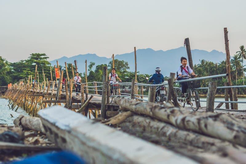 Vietnam, Nha Trang - April 10, 2017: Vietnamese pioneers go home from school on an old wooden bridge stock photo
