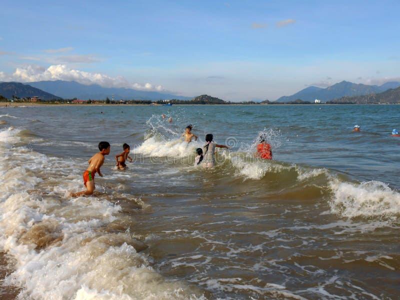 Vietnam, Phanrang: Kinderen die in het overzees zwemmen stock afbeelding