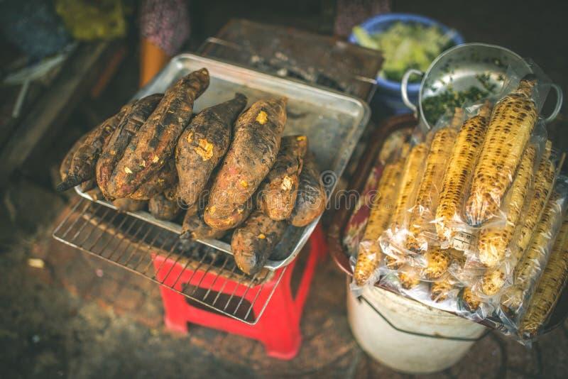 VIETNAM, STREET FOOD - Roadside food stalls, baked sweet potato and corn.  stock images
