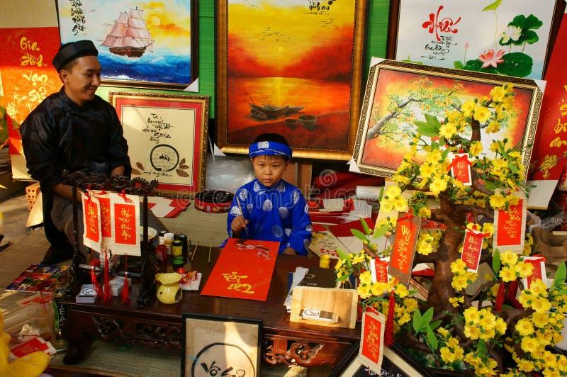 Vietnam tet, asiatisk unge, kalligrafimässa royaltyfria bilder