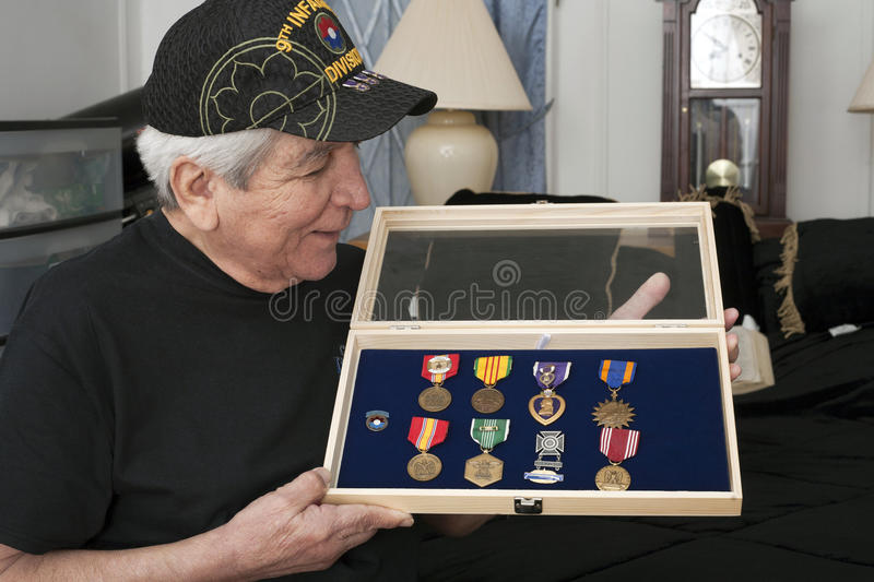 Vietnam vet looks over his medals. BRONX, NEW YORK - MAY 26: Vietnam veteran Franky Gonzalez looks at medals he earned during service. Taken May 26, 2013 in New stock images