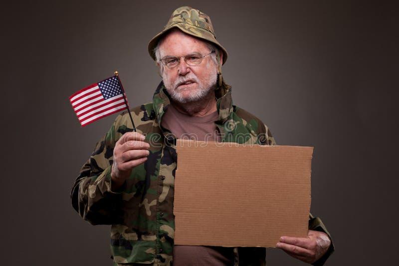 Vietnam Veteran holding a cardboard piece and American flag. Vietnam veteran dressed in camouflage, holding a cardboard piece and American flag stock image